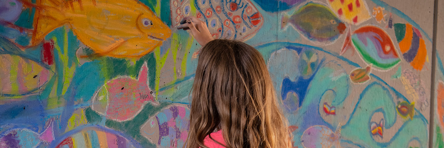 young girl drawing with chalk on cement wall